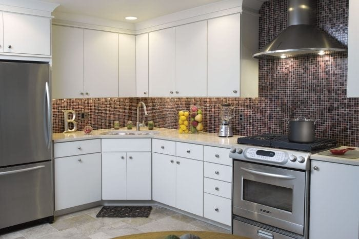 Kitchen with white cabinets and colored tile