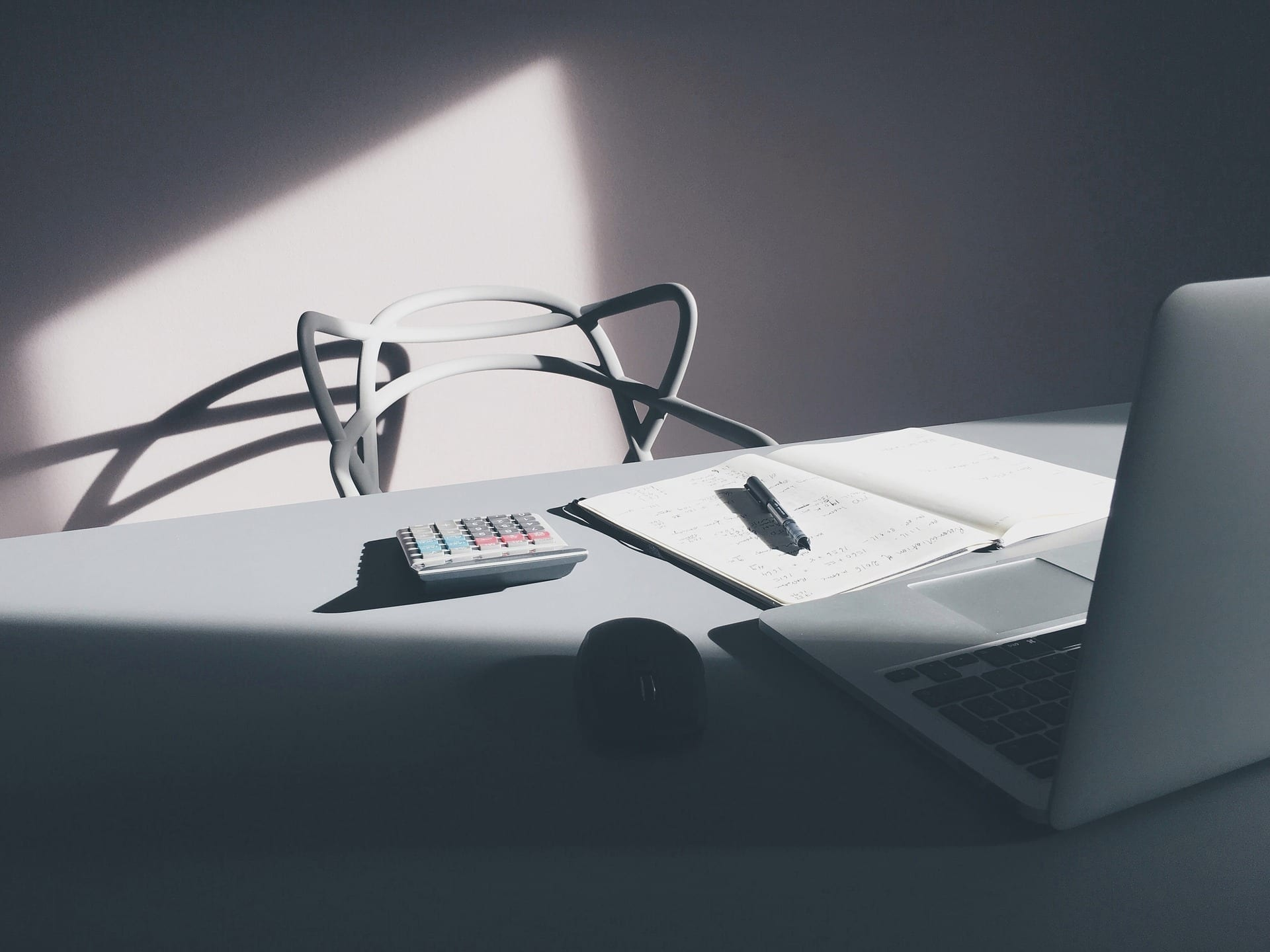 Dark office with white chair behind desk containing calculator and bathroom renovation budget documents